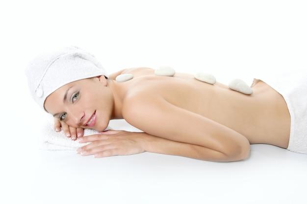Bella donna rilassata sulla spa con trattamento di pietra