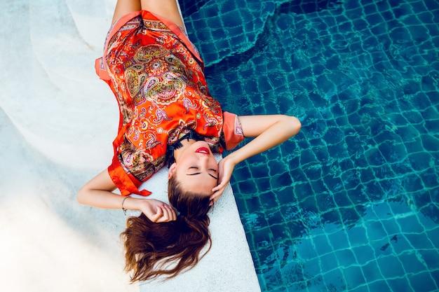 Bella donna rilassata vicino alla piscina