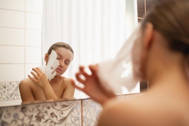 Bella donna rimuove una maschera cosmetica dal viso in bagno vicino allo specchio