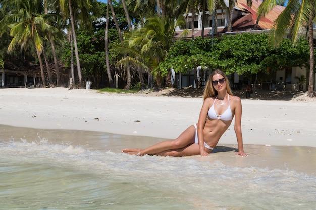 Bella donna russa con lunghi capelli biondi in bikini bianco sulla spiaggia tropicale