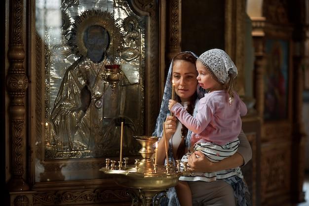 Bella donna russa in una sciarpa e con i capelli rossi in possesso di una bambina e accende una candela di fronte a un'icona nella chiesa ortodossa russa.