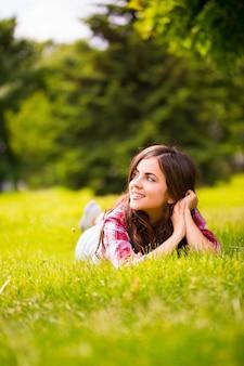 Bella donna sdraiata sull'erba verde