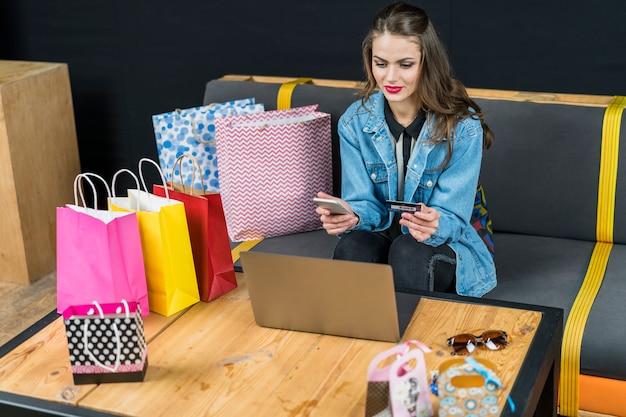 Bella donna seduta a casa con dispositivi elettronici; borse della spesa e carta di credito in mano