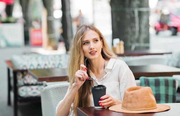 Bella donna seduta in un caffè di strada