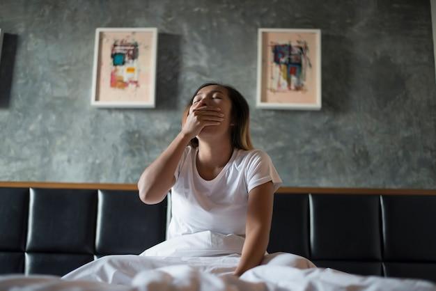 Bella donna seduta sul letto e sbadigliando in camera da letto
