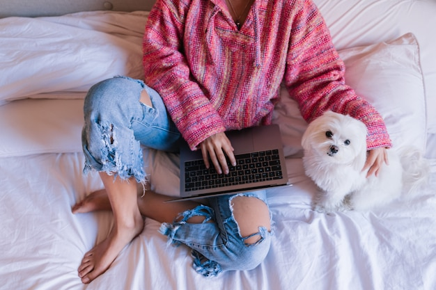 Bella donna seduta sul letto lavorando sul portatile a casa, simpatico cane inoltre