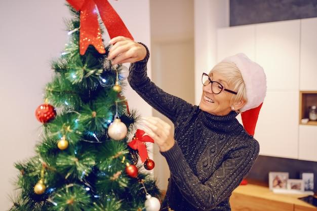 Bella donna senior caucasica con il cappello di santa sulla testa che decora l'albero di natale mentre stando nel salone.