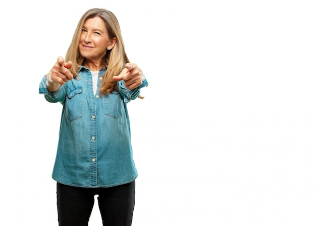 Bella donna senior che sorride felicemente e che indica in avanti con entrambe le mani, scegliendo voi.