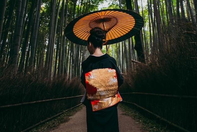 Bella donna senior giapponese che cammina nella foresta di bambù