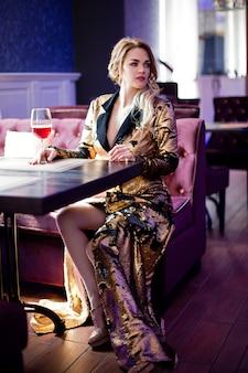 Bella donna sensuale in abiti eleganti, seduto nella caffetteria, bere vino