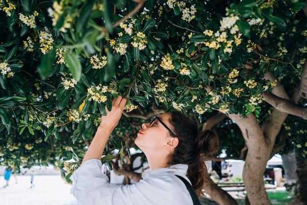 Bella donna sentente l'odore dei fiori degli alberi. tempo di primavera