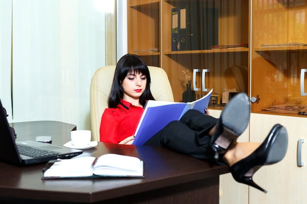 Bella donna seria che legge un documento al tavolo in un ufficio