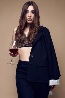 Bella donna sexy del brunette con le labbra succose in biancheria intima scura