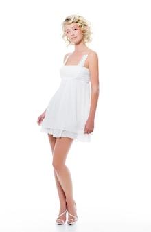 Bella donna sexy di modo con la posa bianca moderna del vestito