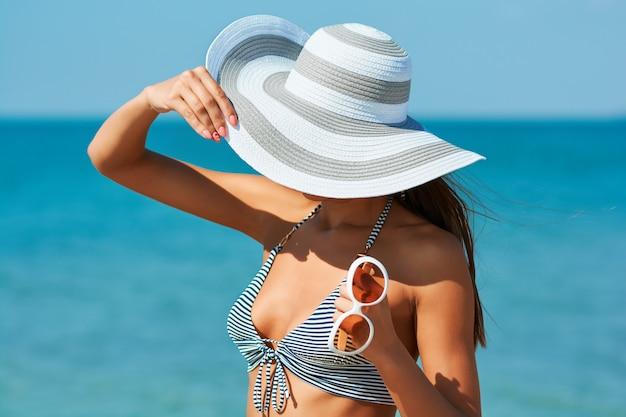 Bella donna sexy in costume da bagno creativo e cappello con occhiali da sole insoliti in riva al mare.