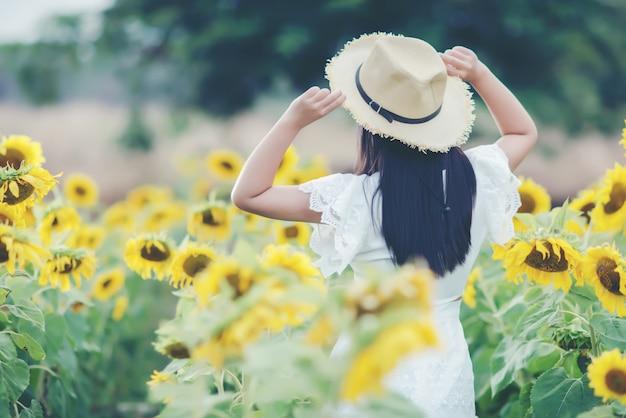 Bella donna sexy in un abito bianco che cammina su un campo di girasoli