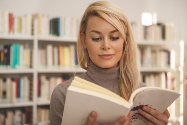 Bella donna shopping per libri presso il negozio