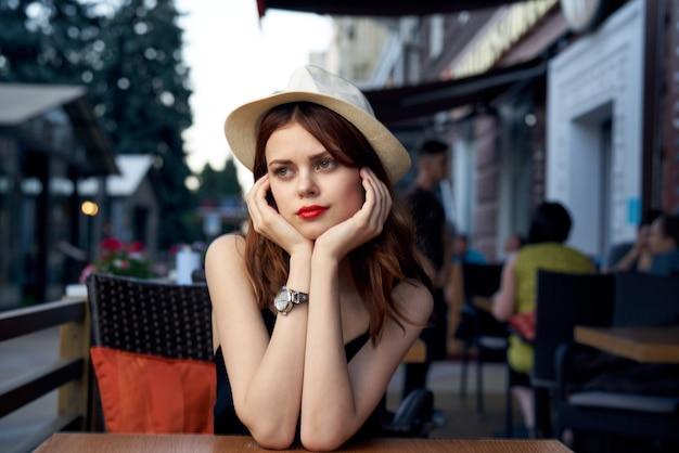 Bella donna si siede a un tavolo in un caffè sul modello di vestito nero cappello trucco luminoso strada.