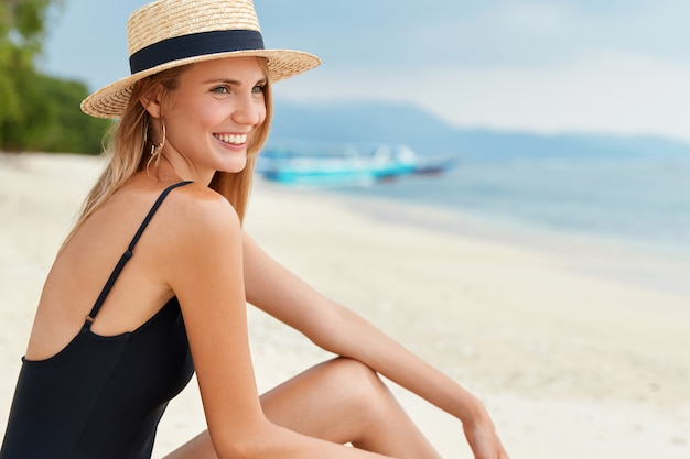 Bella donna si siede sulla spiaggia sabbiosa, vestita in costume da bagno e cappello estivo, guarda il panorama dell'oceano, essendo di buon umore, si rilassa durante una calda giornata tropicale in un paese esotico. sabbia bianca e mare cristallino