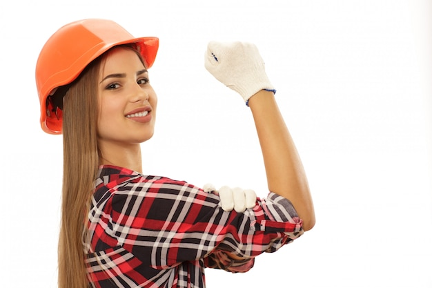 Bella donna sicura con cappello ingegnere protettivo