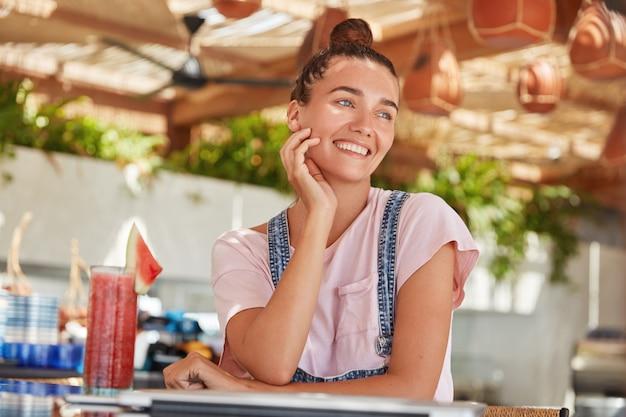 Bella donna sognante con caldi occhi azzurri, sorriso positivo, vestita in modo casual, ha i capelli scuri legati in nodo, beve cocktail freschi, è contenta di trascorrere il tempo libero in mensa. riposo estivo, tempo libero