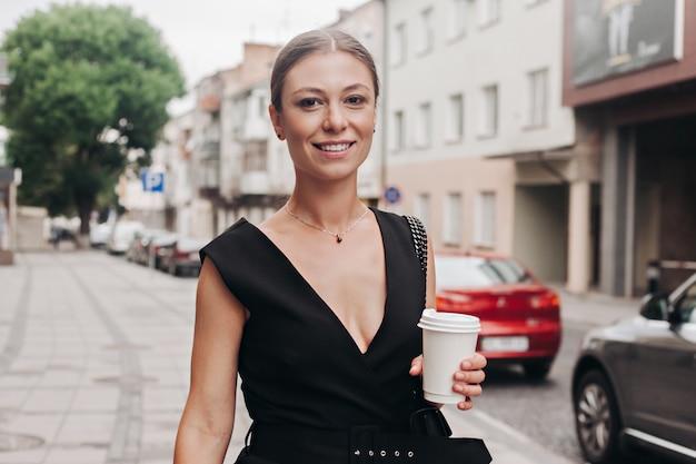 Bella donna sorridente che cammina sulla strada affollata della città dal lavoro con la tazza di caffè