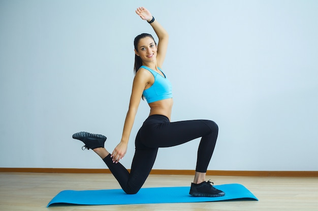 Bella donna sorridente che fa yoga all'interno in palestra