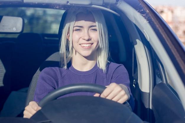 Bella donna sorridente che guida auto, ragazza attraente che si siede in automobile.