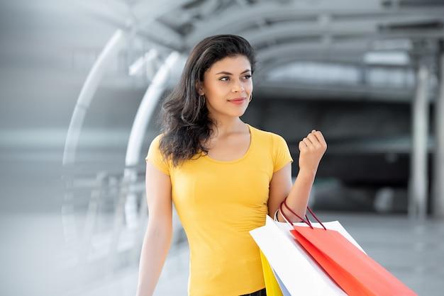 Bella donna sorridente che porta i sacchetti della spesa variopinti