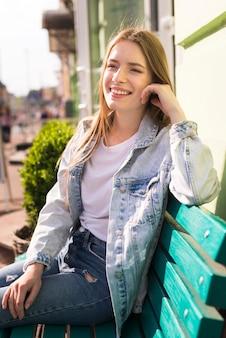 Bella donna sorridente che si siede sul banco all'aperto