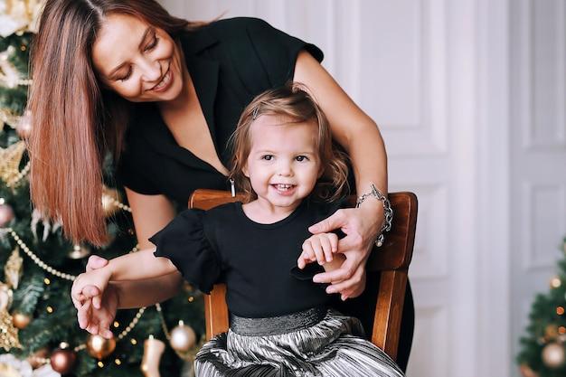 Bella donna sorridente con la sua bambina divertente vicino all'albero di natale