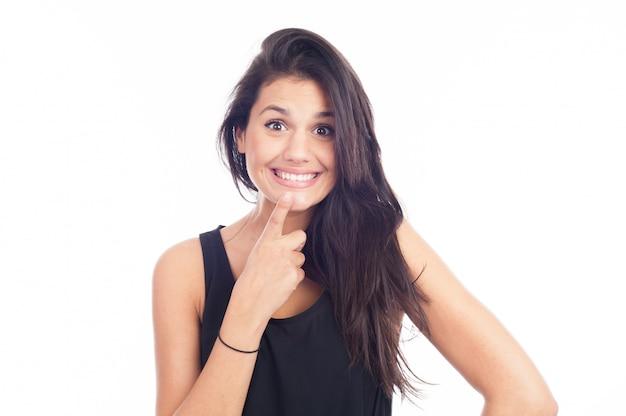Bella donna sorridente con pelle pulita, trucco naturale e denti bianchi su sfondo bianco