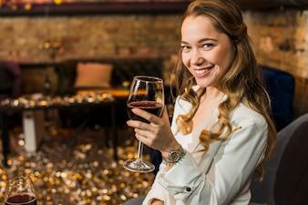 Bella donna sorridente con un bicchiere di vino