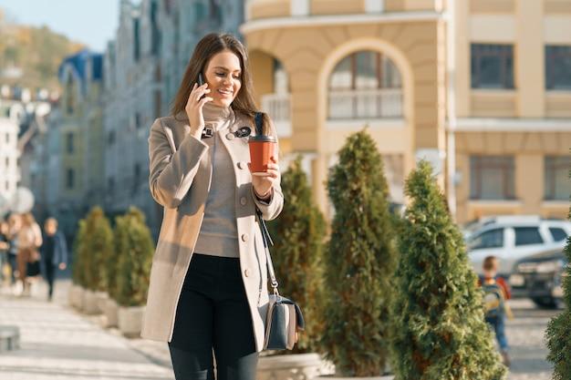 Bella donna sorridente dei giovani che cammina sulla via