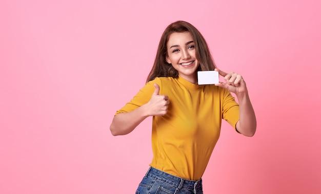 Bella donna sorridente dei giovani in camicia gialla che mostra la carta di credito a disposizione sopra fondo rosa