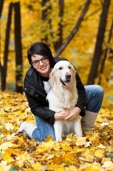 Bella donna sorridente del brunette con il golden retriever nella sosta di autunno.