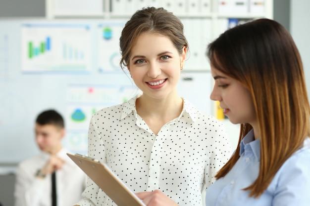 Bella donna sorridente dell'impiegato durante il processo di lavoro in ufficio