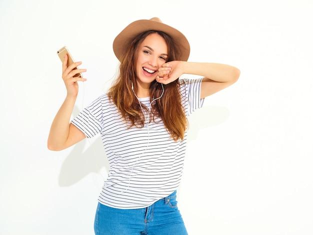 Bella donna sorridente della donna del brunette in vestiti casuali di estate dei pantaloni a vita bassa senza trucco in musica d'ascolto del cappello marrone in telefono con le cuffie isolate su bianco