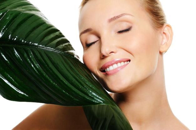 Bella donna sorridente e foglia verde fresca