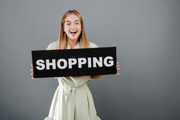 Bella donna sorridente felice con il segno di acquisto isolato sopra grey