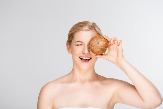 Bella donna sorridente nella noce di cocco della tenuta della stazione termale