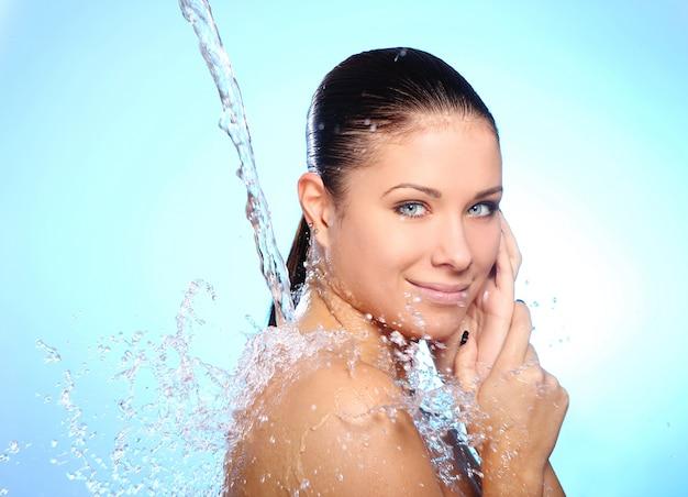 Bella donna sotto spruzzi d'acqua