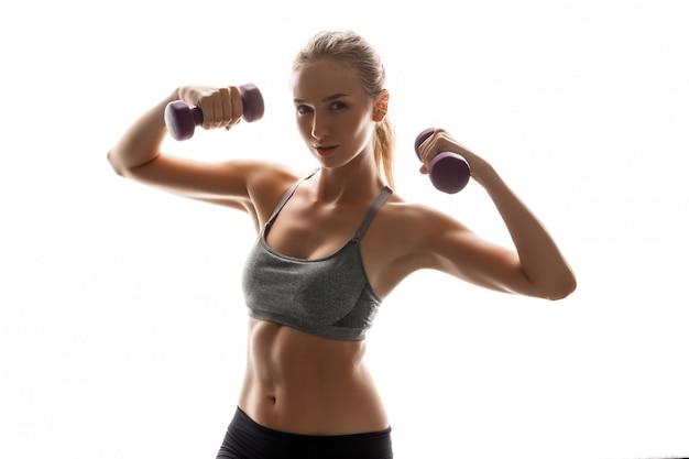 Bella donna sportiva allenamento con manubri
