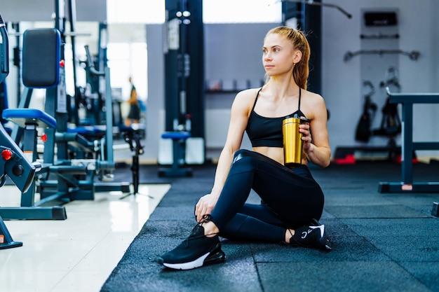 Bella donna sportiva atletica che si siede dopo alcuni esercizi e beve frullato di proteine.
