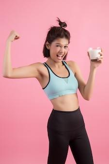Bella donna sportiva che beve latte