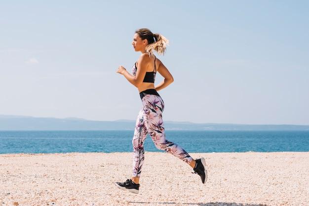 Bella donna sportiva che corre lungo la bellissima spiaggia sabbiosa