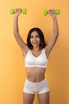 Bella donna sportiva che si esercita con il dumbbell
