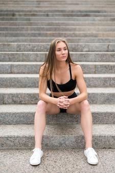 Bella donna sportiva che si siede sulle scale e che osserva via