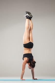 Bella donna sportiva che sta nella posa dell'acrobata