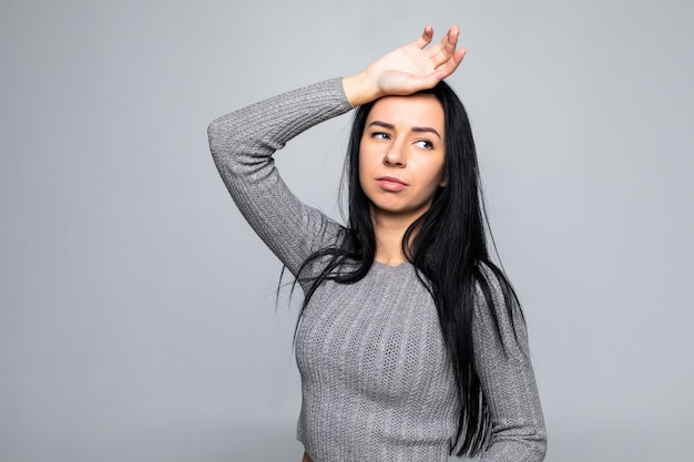 Bella donna stanca sul lavoro, isolata su una parete grigia